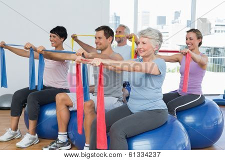 Class holding out exercise belts while sitting on fitness balls in yoga class