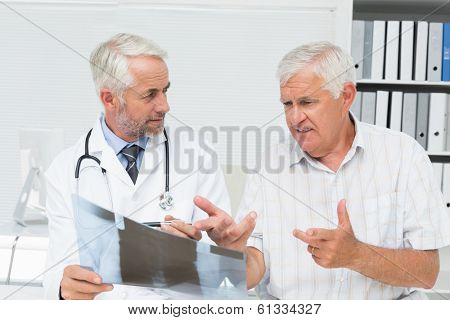 Male doctor explaining x-ray report to senior patient in the medical office