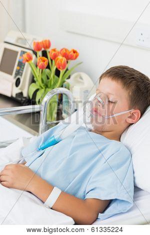 Sick little boy wearing oxygen mask in hospital bed