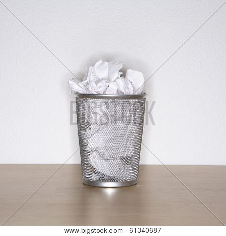 metal waste basket can with crumpled paper