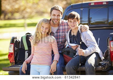 Father And Children Sitting In Truck On Camping Holiday