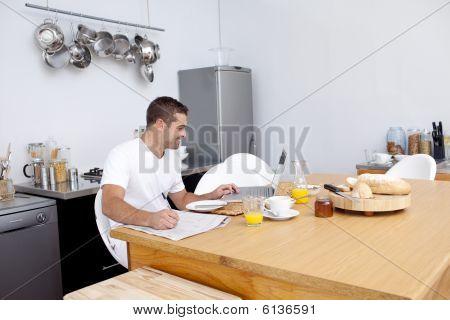 Homem trabalhando na cozinha, enquanto toma o pequeno-almoço