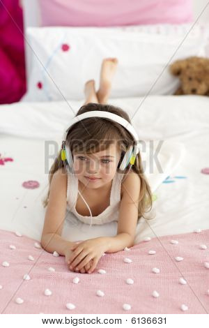 Smiling little girl listening music in bed