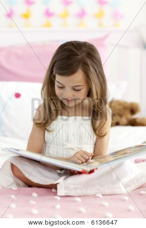 Little Girl Sitting On Bed Reading A Book