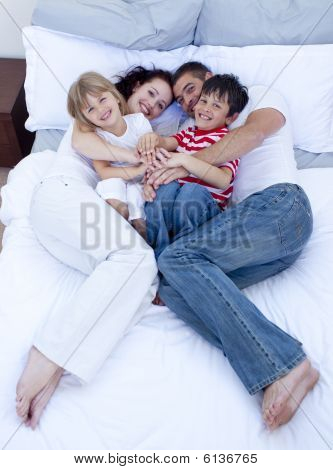 High View Of Parents And Children Relaxing In Bed