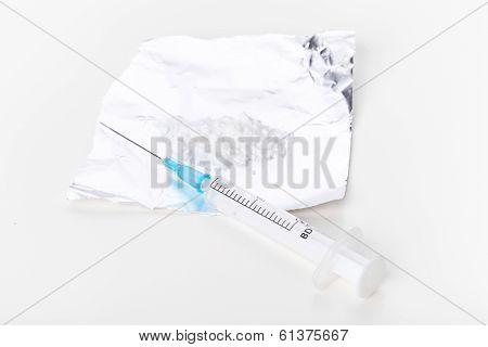 Syringe And Heroin On Foil