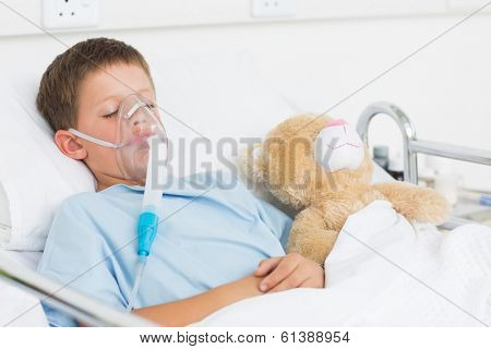 Sick boy wearing oxygen mask sleeping beside teddy bear in hospital bed