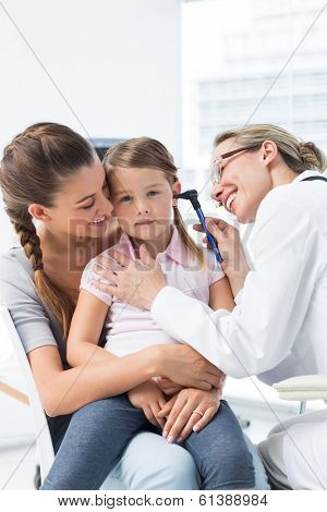 Mother with girl being examined by female pediatrician with otoscope