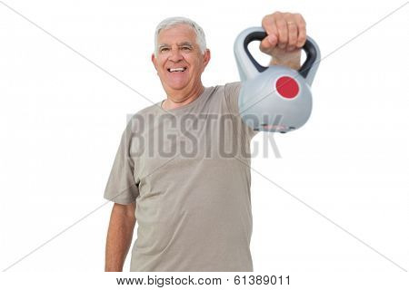 Portrait of a senior man exercising with kettle bell over white background
