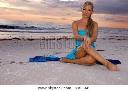 Woman Sitting Cross Legged On Beach