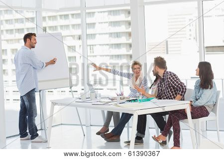 Man presenting an idea to his colleagues in creative office