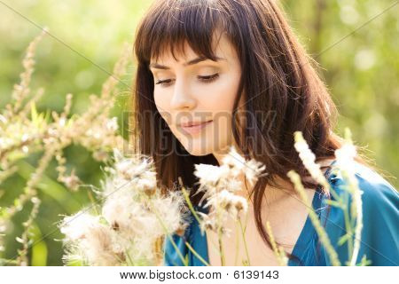 Young Beautiful Girl Among Fluffy Plants