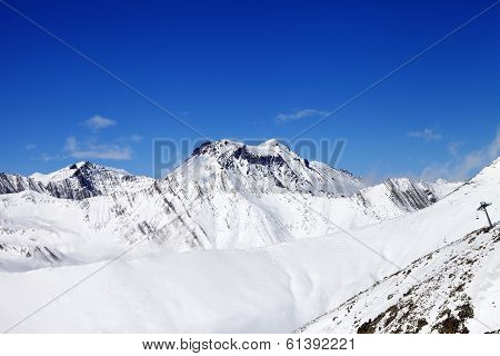Off-piste Slope And Snowy Mounts Against Blue Sky
