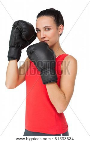 Portrait of a determined female boxer focused on her training over white background