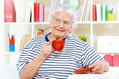 Smiling senior woman sitting at home on a sofa and drinking tea.