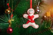 image of ginger man  - Christmas tree with gingerbread man from felt with red heard and red bow - JPG