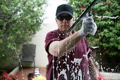 A friendly and professional a window washer soaps and cleans a window with a squeegee, leaving them