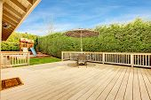 stock photo of chute  - Spacious wooden deck with umbrella and patio table set - JPG