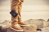 stock photo of winter  - Feet man and vintage retro photo camera outdoor Travel Lifestyle vacations concept