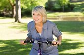 Happy fit woman riding bicycle in parkland