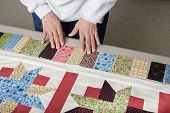 foto of quilt  - A quilter arranges fabric to assemble a piano key border to finish a quilt top - JPG