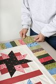 foto of cornerstone  - A quilter arranges a square of fabric for the cornerstone of a quilt top border - JPG