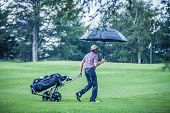 picture of leaving  - Golfer on a Rainy Day Leaving the Golf Course  - JPG