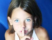 stock photo of shhh  - a caucasian child with her forefinger to her mouth saying shhh to be quiet - JPG