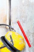 foto of muffs  - Improvement renovation at home. Construction site work tools saw blades cutter to cut tile protective headphones noise muffs