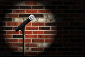 Artistic image of microphone against a rustic brick wall with spotlight effect and copy space.  Clos