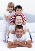 stock photo of children playing  - Happy young parents and children playing in bed together - JPG