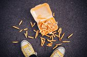 stock photo of big-foot  - Young man has dropped his chips in the street - JPG