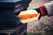 image of dustbin  - Closeup on a hand putting a box of chips in the bin - JPG