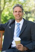 Portrait of happy businessman with disposable coffee cup at park