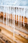 stock photo of chalet  - Long Icicles Melting of a Log Wood Chalet roof top - JPG