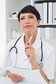 Thoughtful female doctor writing on clipboard at medical office