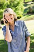 Portrait of happy woman using cell phone in park