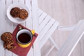 Composition with cup of hot drink and cookies on wooden table background