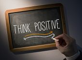 Hand writing the word think positive on black chalkboard