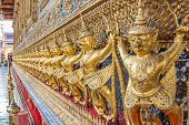 stock photo of garuda  - Guardian Garuda support the base of Wat Phra Kaew Temple of Emerald Buddha in Grand Palace the iconic landmark in Bangkok Thailand