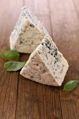 Tasty blue cheese with basil, on wooden table