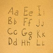 Alphabet (the first part of two) written on a sand beach.