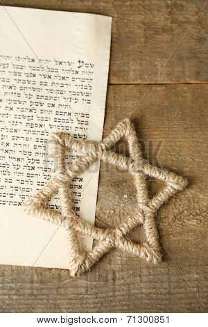 Star of David and page of Genesis book on wooden background