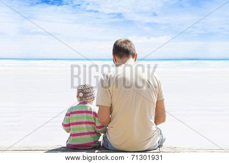 Father And Daughter Sitting On The Beach.