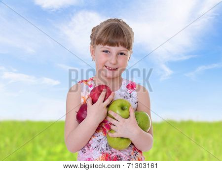 Girl cuddle a lot of big apples.