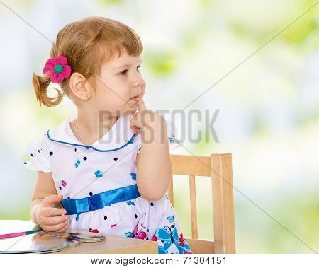 concerned a little girl sitting at the table and looking away.