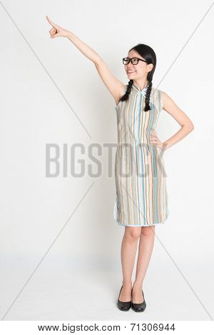 Portrait of full length Asian Chinese girl pointing and looking on blank copy space, in retro revival style cheongsam, standing on plain background.
