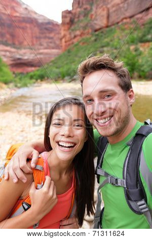 Happy couple taking selfie self-portrait photo while hiking. Two friends or lovers on hike smiling at camera in Zion National Park, Utah, USA. Young Asian woman and Caucasian man.