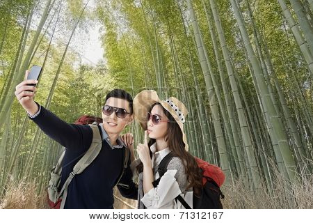 Asian couple travel and selfie in arashiyama bamboo forest, Kyoto, Japan.