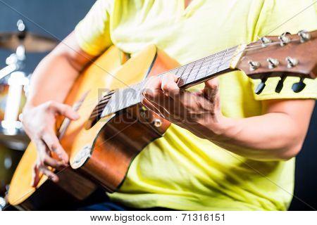 Asian professional guitarist playing acoustic guitar music in recording studio